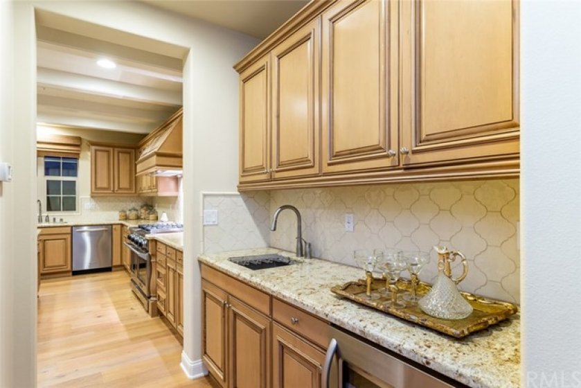 Butlers pantry with sink and wine refrigerator.  Hall leads to walk-in pantry and doorway to 3-car garage.