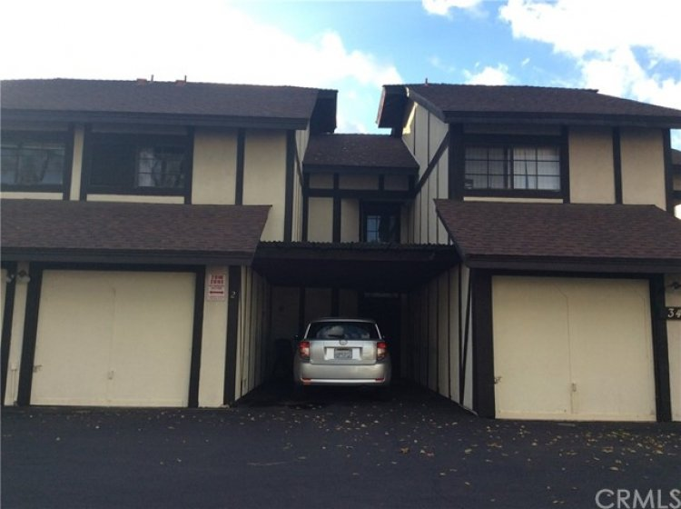 Front of unit showing one car garage and covered parking