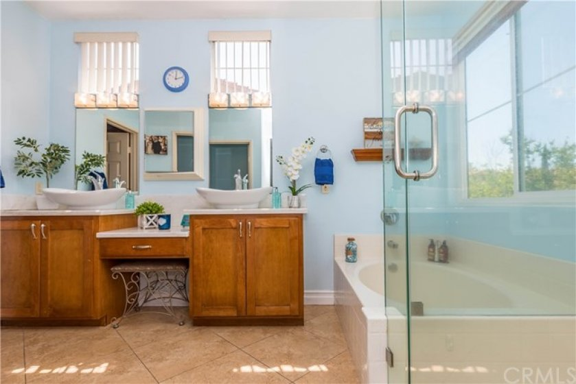 Your updated master bath includes rich, warm vanities, each with a vessel sink and separated by a make up vanity area. Notice the frameless shower enclosure too!