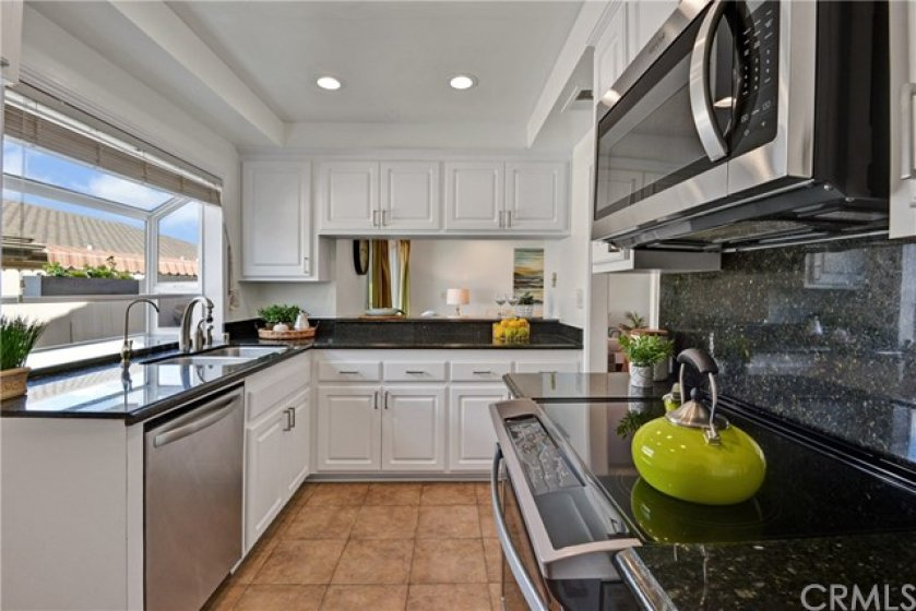 Kitchen is equipped with recessed lighting, new stainless steel appliances and granite counters.