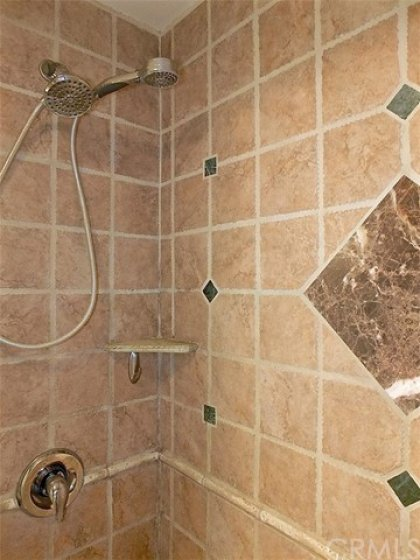 Stall shower is large with custom tile.