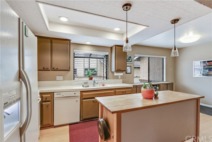 Painted brown cabinets are topped with white ceramic tile.  Recessed lighting and two windows make this work space light, bright and airy.