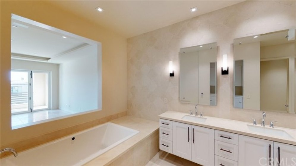 Dual vanities and large soaking tub with full tile accent wall.  Opening between bath and bedroom.