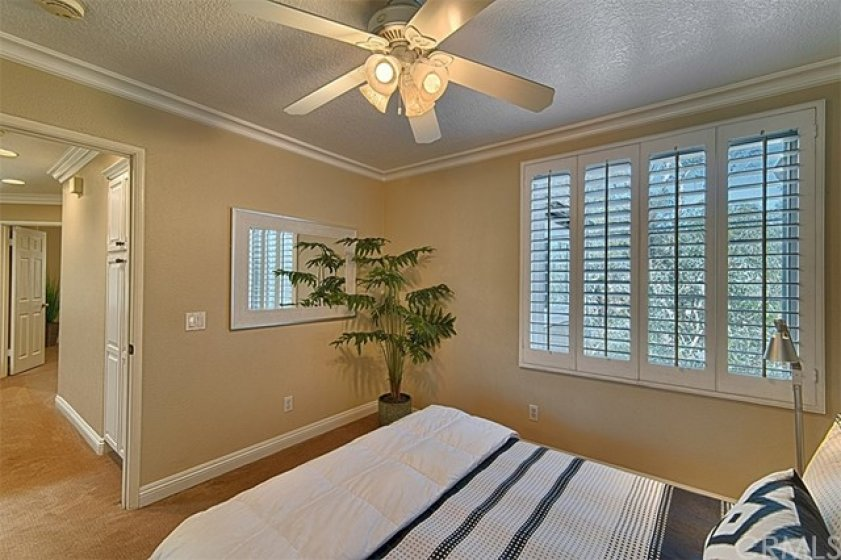 Upstairs suite with plantation shutters, lush carpet, lighted ceiling fan and note the linen storage in the hallway.