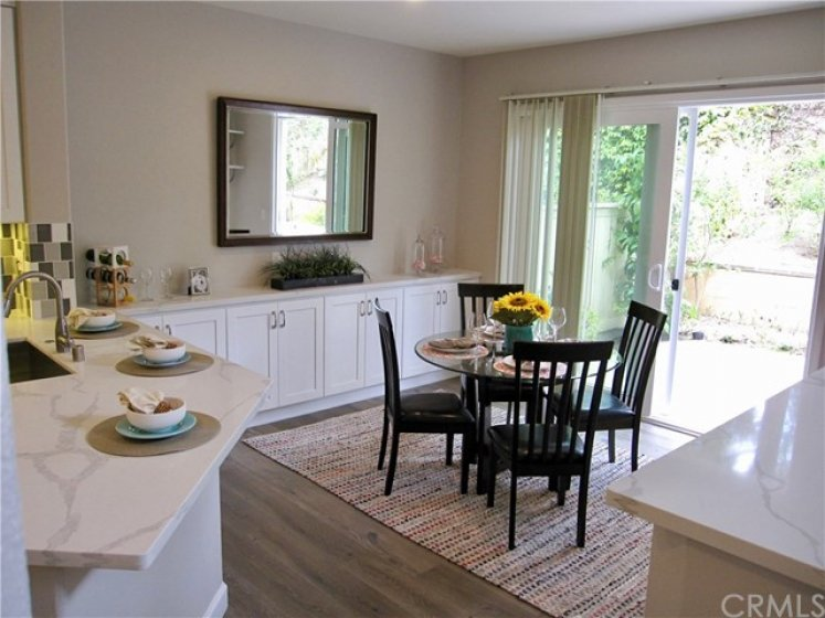 Dining area with all new practical storage cabinets and quartz countertop. Slider door leads to peaceful backyard.