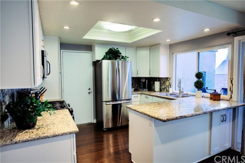 Beautifully upgraded kitchen with white shaker cabinets, granite counters, decorative backsplash, newer microwave, stainless steel appliances, recess lights, crown molding, dual stainless steel sink.
