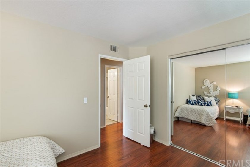 Bedroom No. 1 with laminate flooring, new paint, and mirrored sliding closet doors.