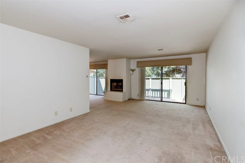Living room with slider, fireplace, and adjacent dining room