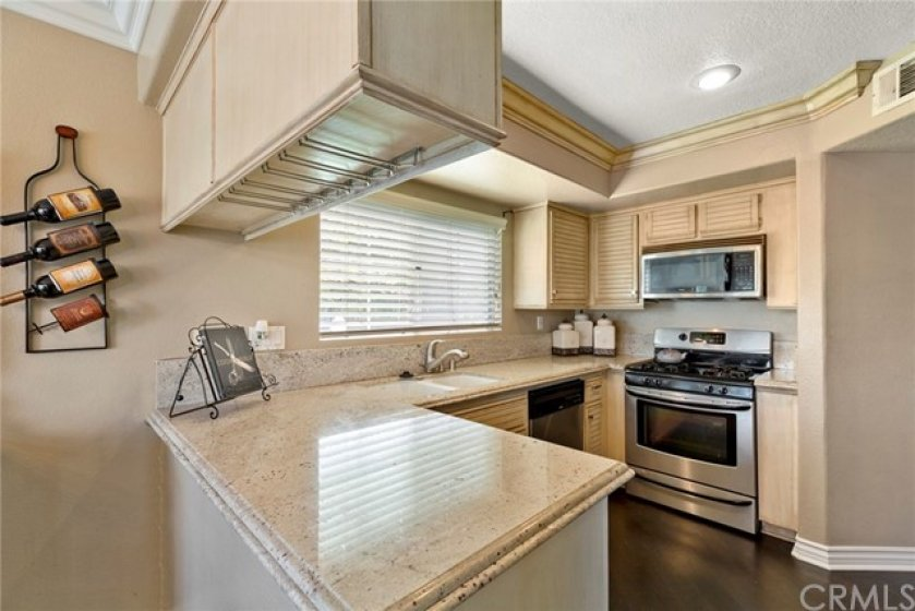 Granite counter tops with bull nose trim & back splash- Stainless steel gas stove & oven, Microwave oven- Crown molding and wood laminated flooring- Under cabinet Wine glass racks