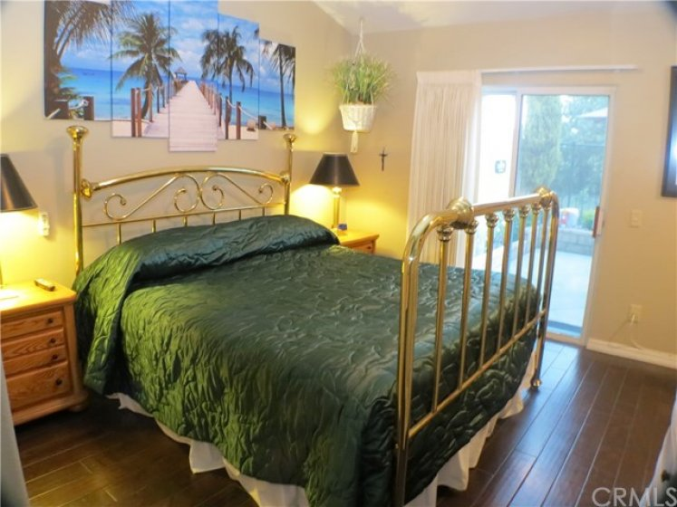 Master suite with hardwood flooring and access to backyard
