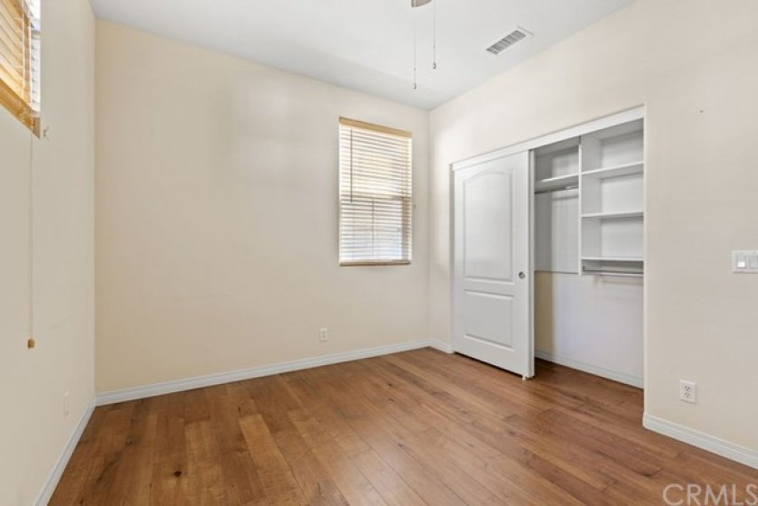 The downstairs bedroom features hardwood floors, wooden blinds and closet shelving.
