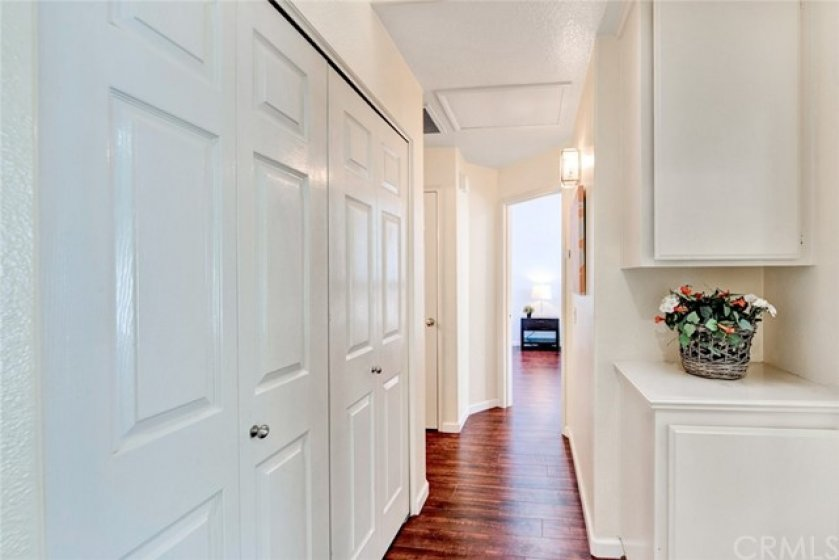 Looking into the hallway, the laundry closet is to the left, linen cabinets to the right, and the opening on the left past the laundry goes to a full bath and a coat closet. Straight ahead is the master suite.