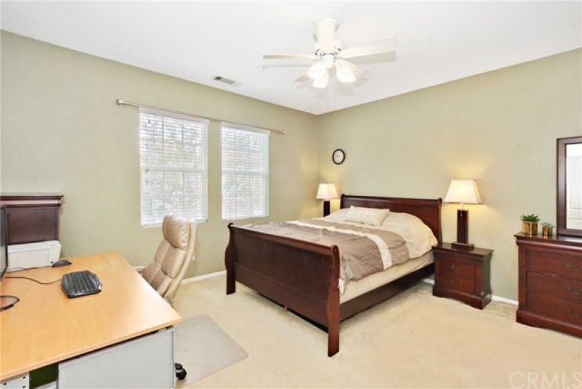 Master Suite with plush carpet, ceiling fan & abundance of natural light from large windows