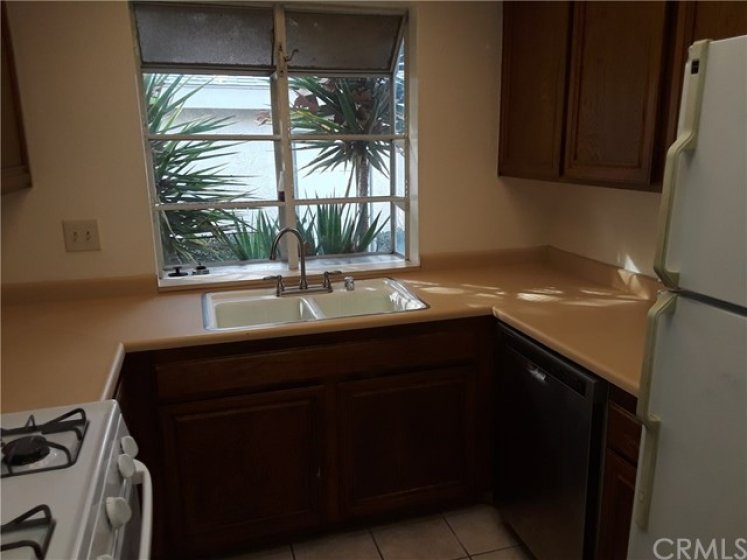 Kitchen features a garden window.