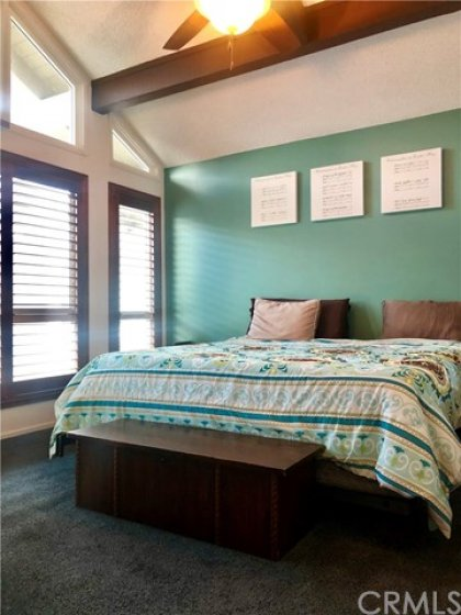 Two large bedrooms with high beamed ceilings on the upper level.