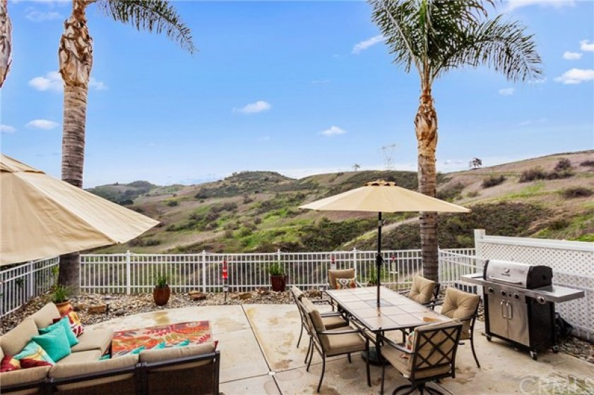 This large backyard space has a private, unobstructed nature view! This is appointed with stamped concrete and easy care desert landscape to help save water!