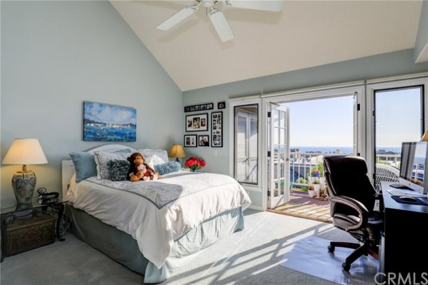 Gorgeous master bedroom with vaulted ceilings, ceiling fan and french doors opening onto the balcony with panoramic views!