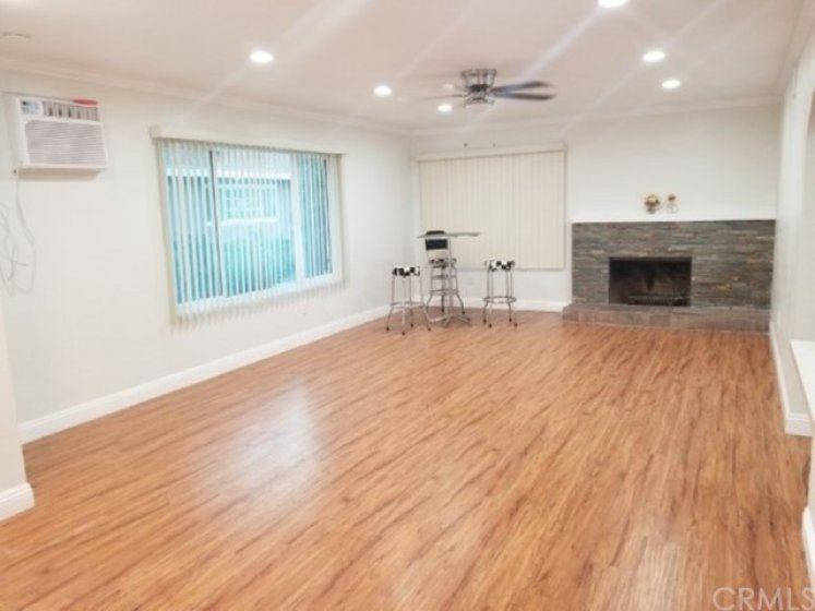 Open Floor Plan Spacious Living Room w/ Brick Gas Fireplace. BRAND NEW laminated wood flooring, baseboards, crown moulding, recessed lights, ceiling fan and wall air and interior paint.  BRAND NEW double pane windows and mini-blinds thruout.  View#1
