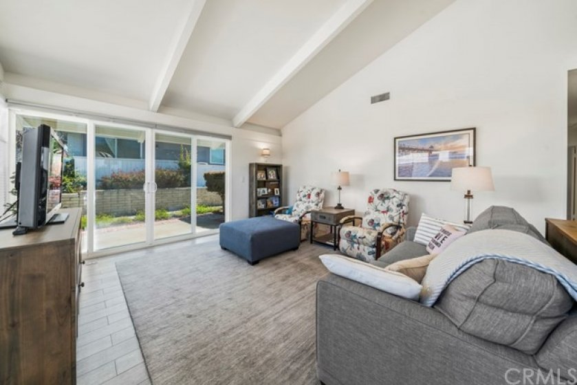 Very open and spacious living room.  High beamed ceilings and a brand new sliding door to the patio area.