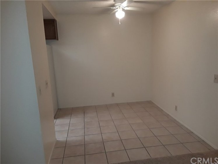 Dining area has ceiling fan and tile floors.