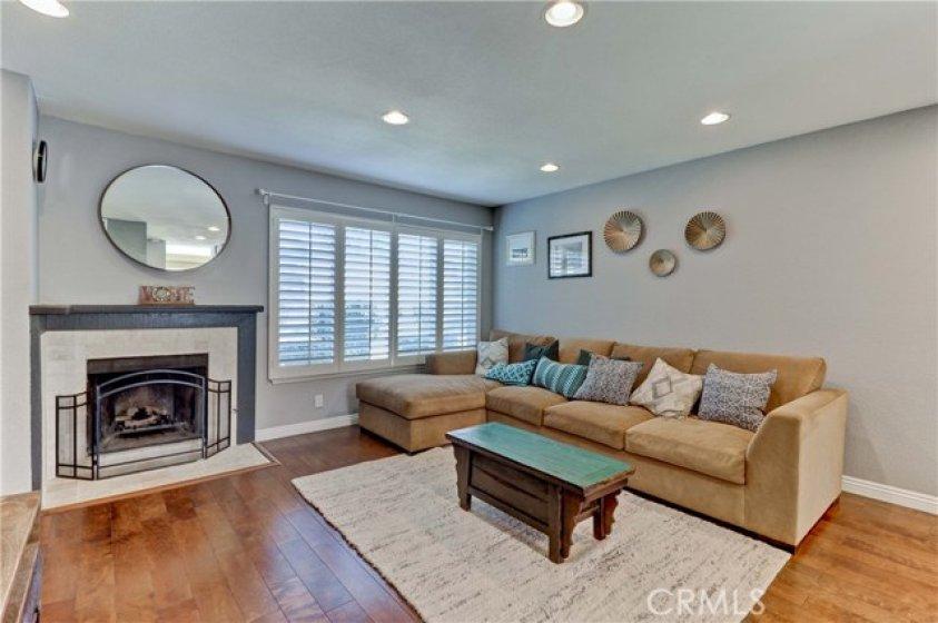 Elegant fireplace, plantation shutters, laminate flooring and recessed lighting