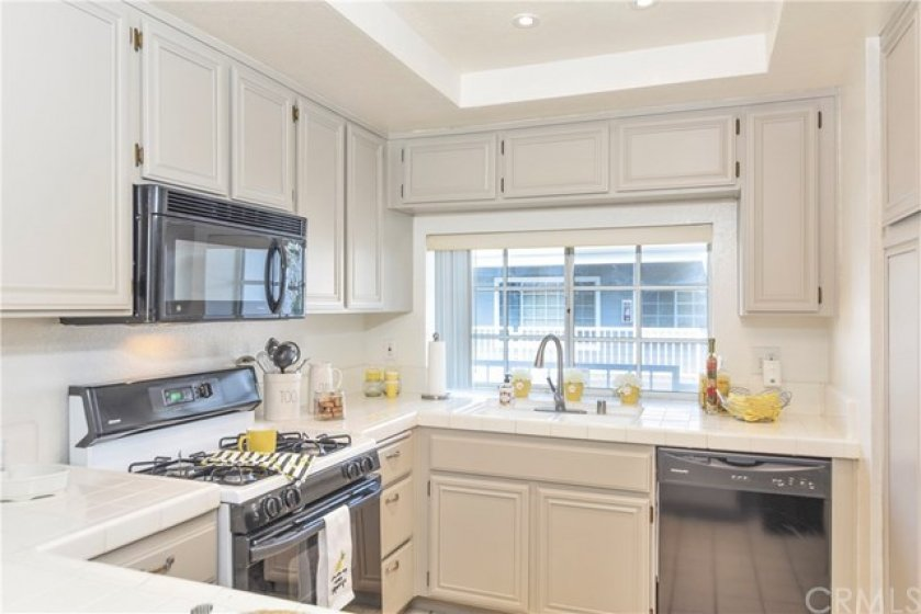 Kitchen has large sunny window & recessed lights