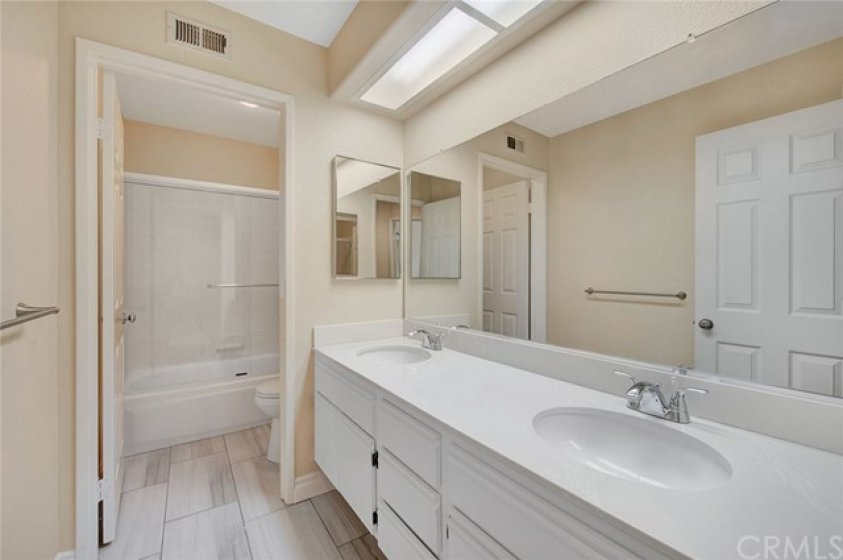 Guest bathroom with dual sink and separate shower/bathtub area