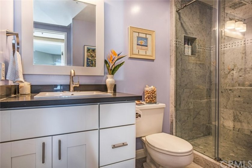 Newly remodeled 2nd bath with stunning glass shower enclosure with rolling door and custom marble tile work and quartz counter tops and new cabinetry. Everything is new and stunning!