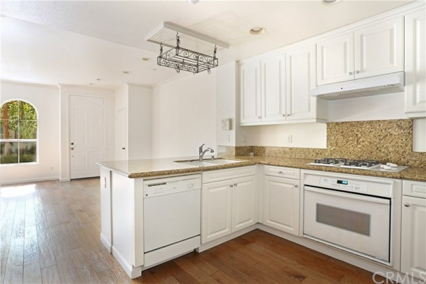 The kitchen opens up to the living room where there is ample room for a dining table and three stools that can be stored under the opposite side of the sink for more casual morning breakfasts.