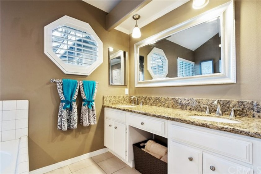 This master bath also has dual sinks with storage and a framed vanity mirror