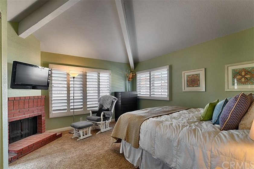 Master Bedroom, with beamed ceilings, plantation shutters, and fireplace.