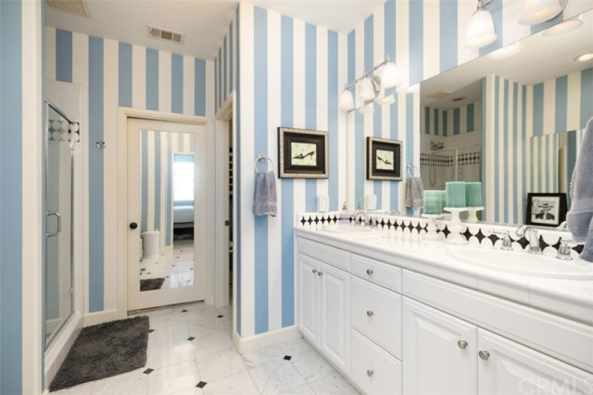 Large master bathroom with dual sink, two walk in closets, and vanity.