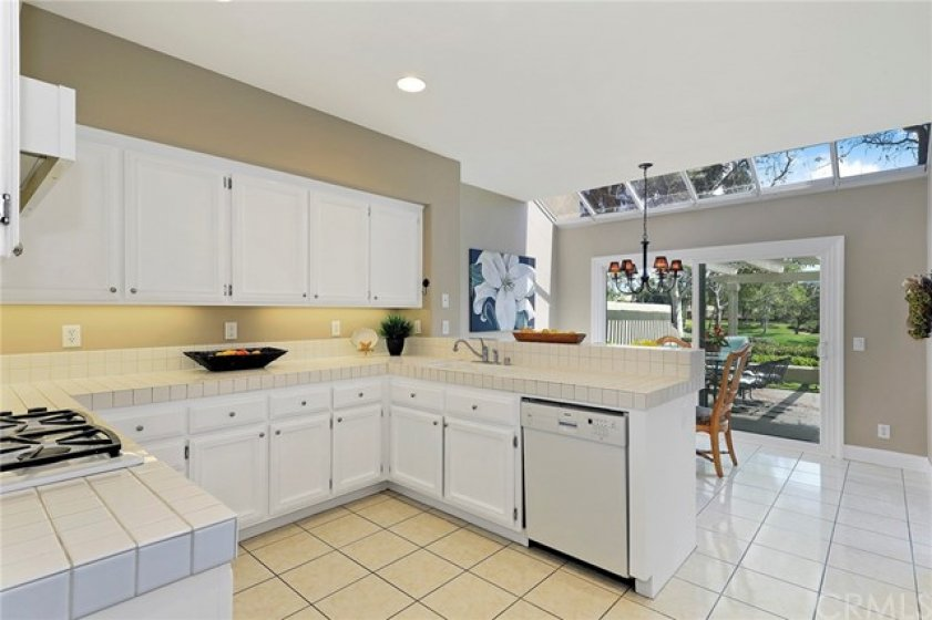 Bright open kitchen with lots of cabinets, stove top and recessed lighting