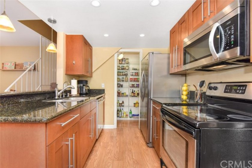Kitchen shows pantry  at the back which has a sliding door.