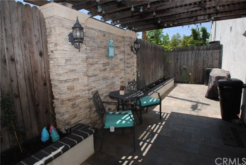 Back patio stacked stone accent wall with wood pergola