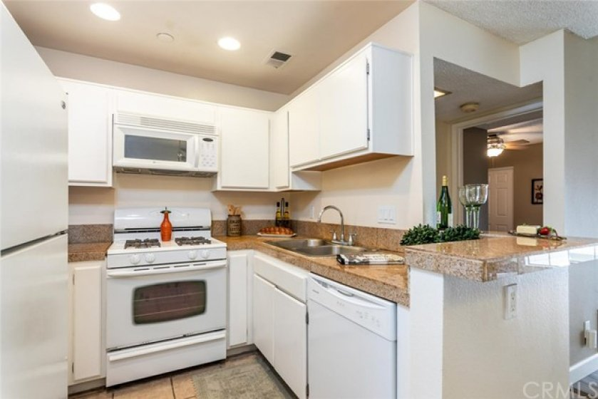Kitchen with granite counters, built-in microwave, tile flooring and recessed lighting.
