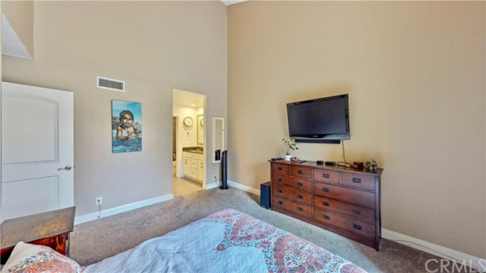 Master bedroom with vaulted ceilings and direct patio access.