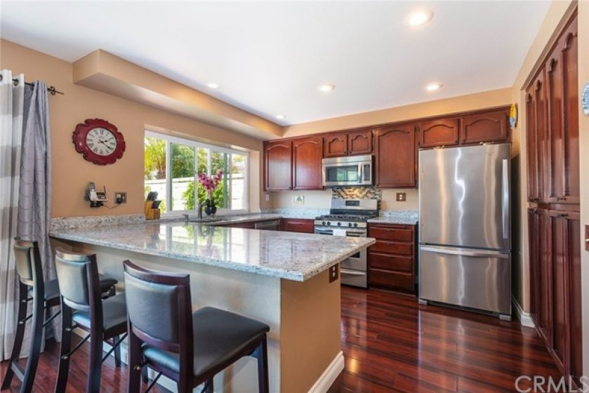 Remodeled kitchen boasts granite counters, custom granite & crackled glass back splash, rich wood cabinetry, newer kitchen window, recessed lighting, and newer SS appliances.
