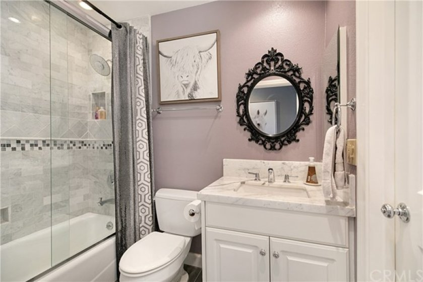 Second full bath has new custom tile, marble counter tops, shower/bathtub combination.