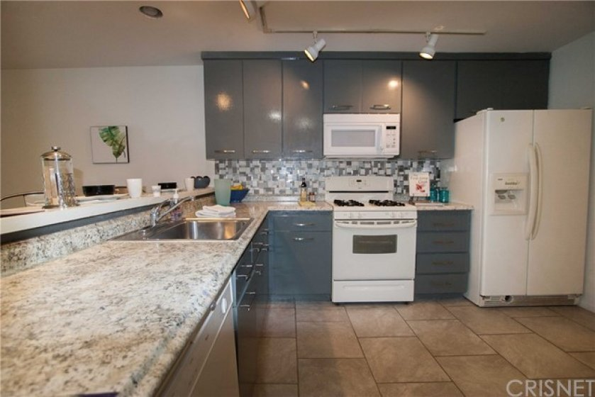 Updated kitchen with grey neutral granite countertops and glass backsplash!