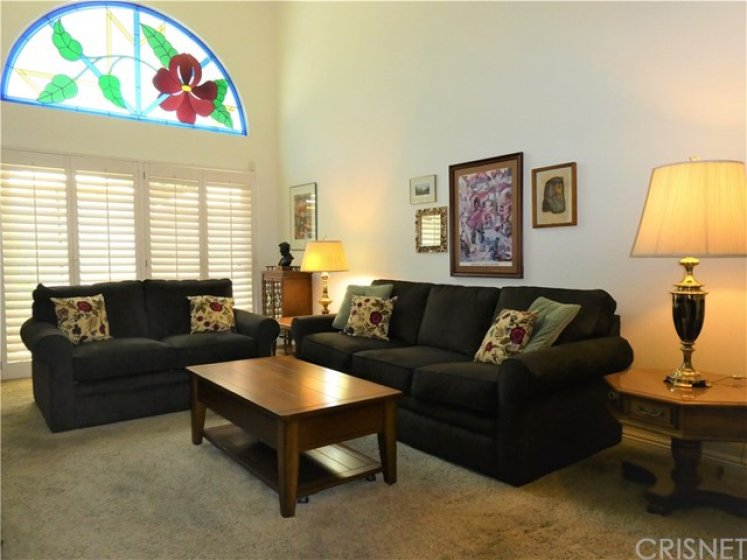 Spacious living room with vaulted ceiling and Tiffany style arched clerestory window