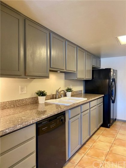Spacious kitchen with great cabinet space, granite countertops, beautifully maintained appliances, including a new black stainless steel microwave.