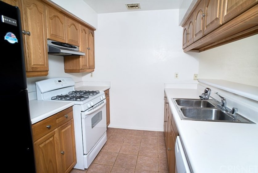 Lovely galley kitchen with gas oven, a dishwasher, vent hood and refrigerator.