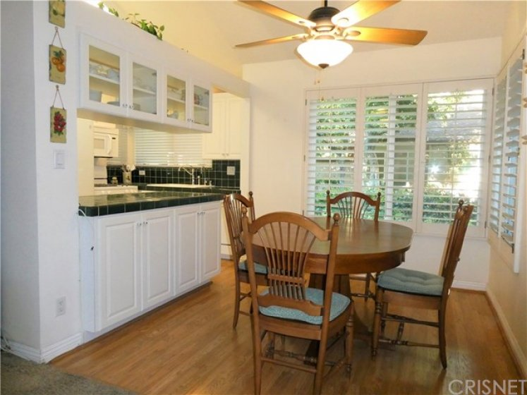 Dining area with large picture windows on two sides, laminate flooring, plantation shutters and adjoining kitchen large peninsula counter and cabinets.
