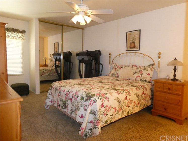 Spacious master bedroom, with two mirrored wardrobe closets and adjoining dressing area vanity and bath.