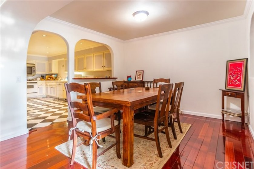 Formal dining room through archway with view into kitchen. Teak flooring throughout.