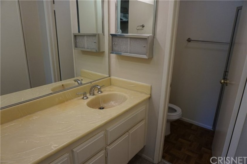 Bathroom #1 in master bedroom with plenty of counter space and cupboards. Toilet and shower separate from sink area.
