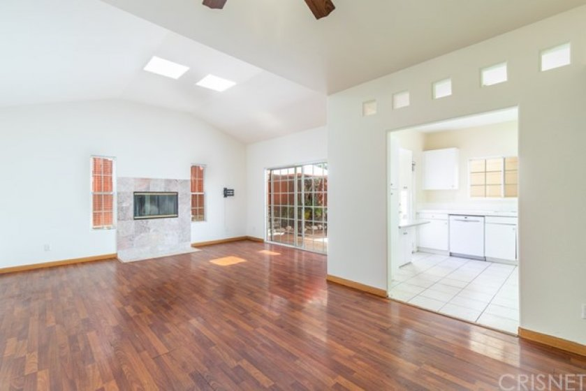 Living Room - Wood Tone Laminate Floor, Wood Burning Fireplace, Kitchen Adjacent