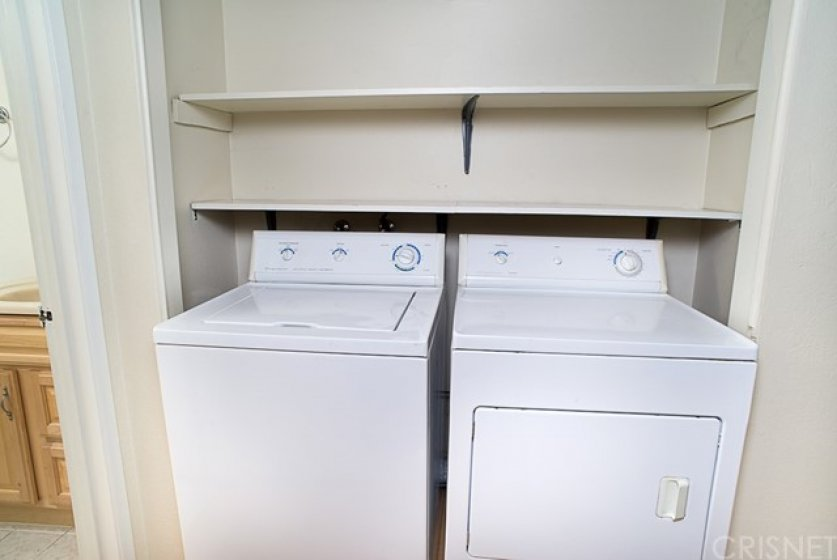 Indoor laundry area downstairs with storage.
