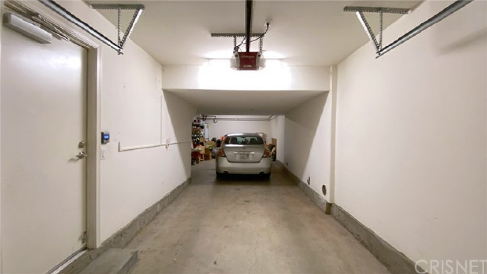 Large tandem parking garage with tons of storage space at the end of the garage.